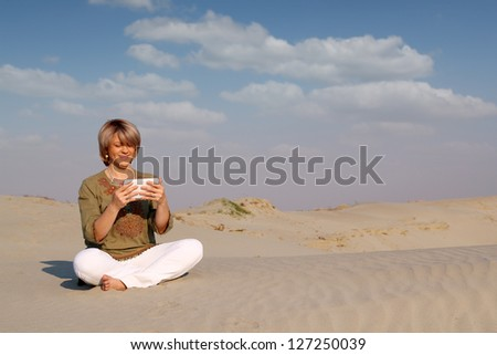 beautiful woman with tablet pc in desert