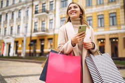 Beautiful woman with telephone enjoying shopping in the city street. Happy girl after shopping with colorful shopping bags in the street. Consumerism, purchases, shopping, lifestyle concept.