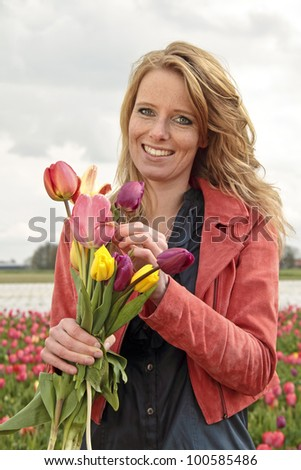Beautiful woman with tulips in the tulip fields in the Netherlands