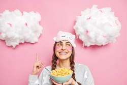 Beautiful woman with two pigtails dressed in pajama indicates upwards holds bowl of cereals has healthy breakfast applies collagen patches under eyes isolated over pink background clouds above