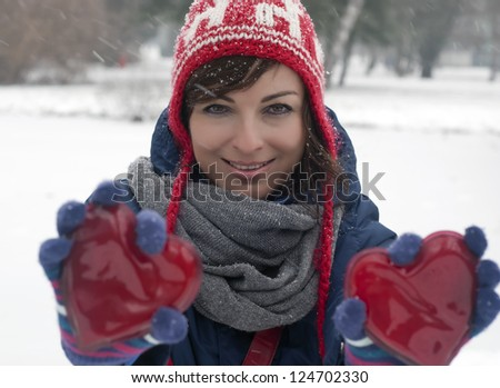 Beautiful woman with two red hearts in the snowy park.