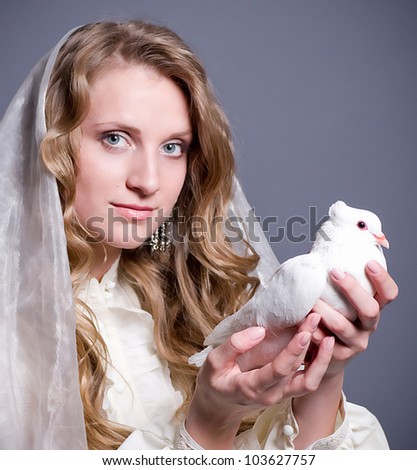 Beautiful woman with white dove on dark background