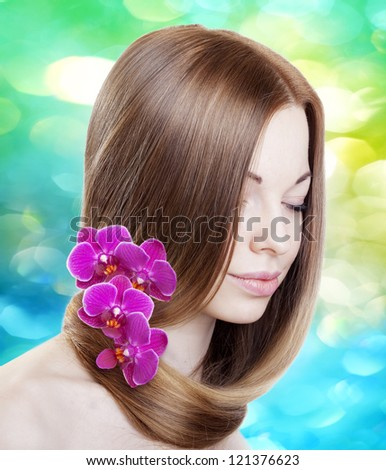 Beautiful woman with with orchids in her gorgeous hair