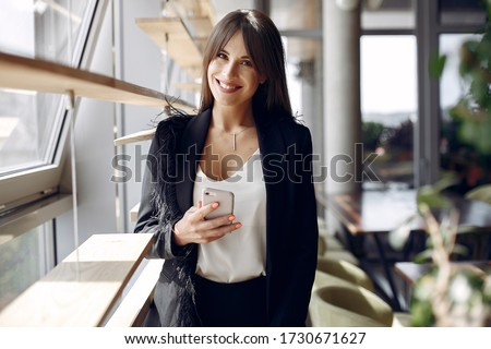 Beautiful woman working. Busineswoman in a stylish clothes. Woman standing near window with phone