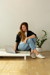 Beautiful woman working on a laptop in minimalist interior apartment