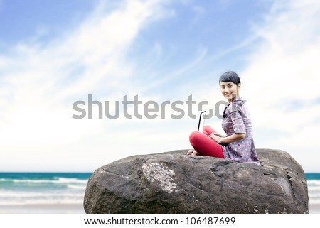 Beautiful woman working on laptop at the beach. shot outdoor