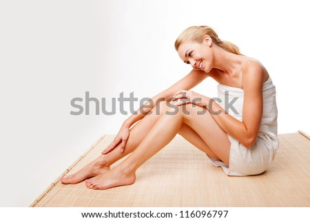 Beautiful woman wrapped in a towel caressing her smooth silky legs with a gentle smile as she relaxes after a treatment at a spa