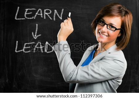 Beautiful woman writing a motivational concept on a blackboard
