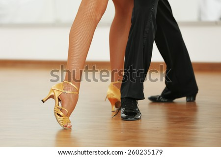 Beautiful womanish and masculine legs in active ballroom dance, indoors #260235179