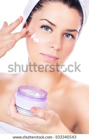 Beautiful women applying moisturizer cosmetic  cream on face