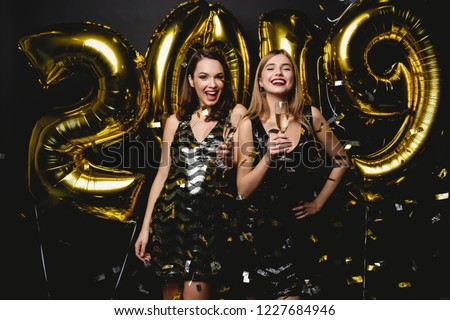 Beautiful Women Celebrating New Year. Happy Gorgeous Girls In Stylish Sexy Party Dresses Holding Gold 2019 Balloons, Having Fun At New Year's Eve Party. Holiday Celebration