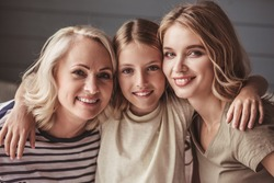 Beautiful women generation: granny, mom and daughter are hugging, looking at camera and smiling while sitting on couch at home