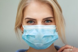 Beautiful Women In A Medical Mask. Close-up of a young woman with a surgical mask on her face against SARS-cov-2.
