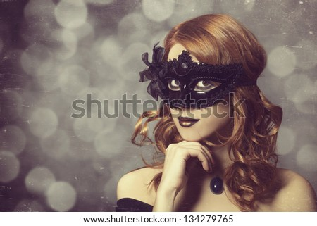 Beautiful women in carnival mask. Photo in vintage style.