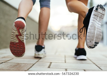 Beautiful women jogging on pavement in city and feets are in focus #567326230