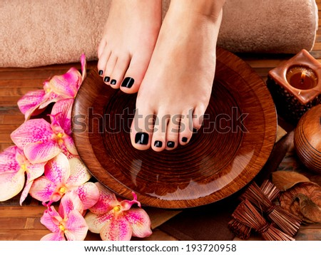 Beautiful women legs with black pedicure after Spa procedures Spa treatment concept