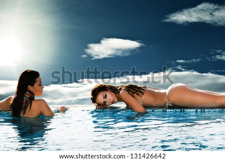beautiful women relax in pool sky with sun and clouds in background