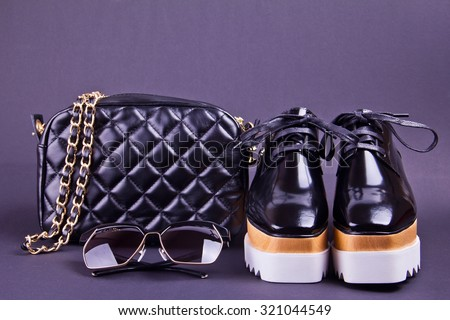beautiful women\'s minimal set of fashion accessories on a black background. Ideal for blogs or magazines. Sunglasses, purse, shoes.