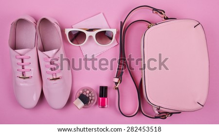 beautiful women\'s minimal set of fashion accessories on a pink background: shoes, sunglasses, perfume, nail polish and handbag. Ideal for blogs or magazines. Mock up.