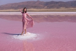 Beautiful women tourist in pink long dress walking in water on pink salt Lake Tuz. Ankara. Tuz Golu Lake is the second largest lake in Turkey and one of the largest hypersaline lakes in the world