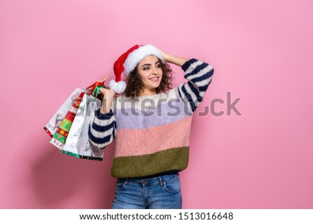 Beautiful women wearing bright Christmas carrying colorful shopping bags. On pink background. Christmas shopping And happy new year. There are many discounts many stores around the world.