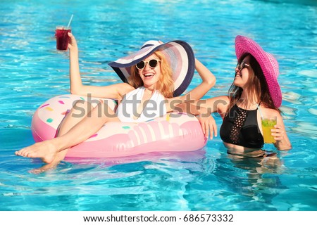 Beautiful women with cocktails relaxing in pool