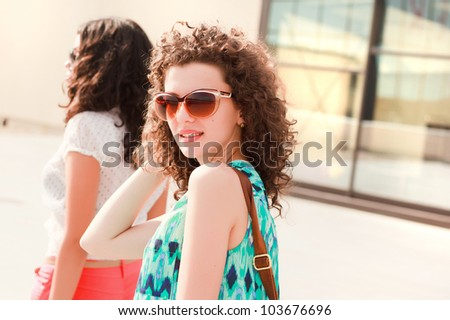 beautiful women with curly hair posing outdoor on a sunny day