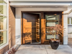 Beautiful Wood Door as Entrance to New Luxury Home: Large and Wide Hardwood Door with Windows and Potted Plant to Right of Door in Exterior of Beautiful House. Cement Patio. Door is Slightly Ajar/Open
