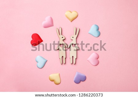 beautiful wooden bunnies as happy couple of lovers and colorful handmade heart on pink background, creative Valentine's day card, love, dating and family concept, flat layout #1286220373