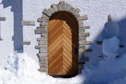 Beautiful wooden door of roman catholic chapel at mountain Gornergrat, Zermatt, Switzerland. Photo taken March 23rd, 2021, Zermatt, Switzerland.