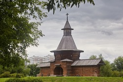 Beautiful wooden fortress made of logs, tower with entrance wolves on the background of the summer landscape and gray sky. Traditional old architecture of the north of the Middle Ages.