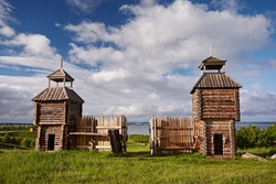 Beautiful wooden fortress made of logs with a tower against the background of the summer landscape and blue sky with white clouds. Traditional Old Architecture of the Middle Ages North