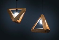 Beautiful wooden geometric modern ceiling lamp interior contemporary decoration isolated on a dark background.