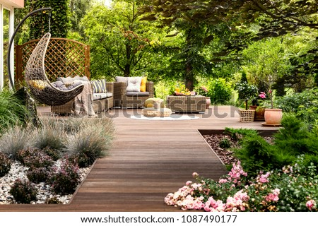 Beautiful wooden terrace with garden furniture surrounded by greenery on a warm, summer day #1087490177
