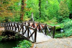 Beautiful wooden vintage bridge across small river in the autumn Sofia Park, Uman, Ukraine. landscape in the fall. Calendar, postcard of the seasons, October, November