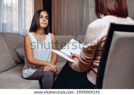 Beautiful worried woman at a psychologist appointment. Psychological problems. Mental problems concept Foto stock ©