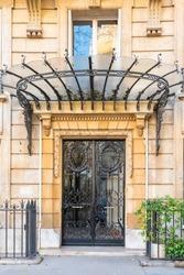 beautiful wrought iron door in Paris, in an avenue of a chic neighborhood