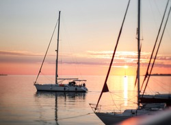 Beautiful yacht sailing into the sea from the pier against the background of an orange sunset