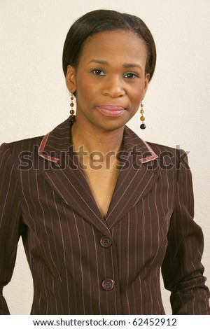 Beautiful 25 year old african american woman in suit behind office chair.