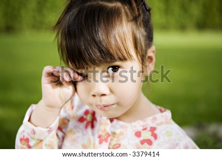 Beautiful 3-Year-Old Girl with a Sad Expression in her Backyard