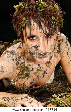 Beautiful 30 year old woman covered in mud and moss over black.