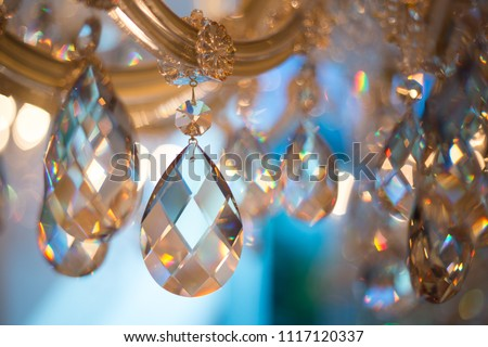 Beautiful Yellow and blue Light reflecting through brushed czech glass crystals hanging on vintage chandelier
