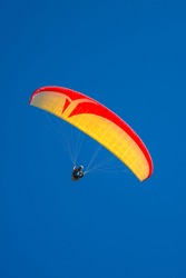 Beautiful yellow and red paraglider flying in blue sky, paste space, smooth background