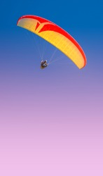 Beautiful yellow and red paraglider flying in colorful sky, paste space, smooth gradient background