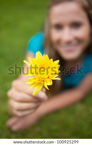 Beautiful yellow flower held by an attractive young girl lying in a park