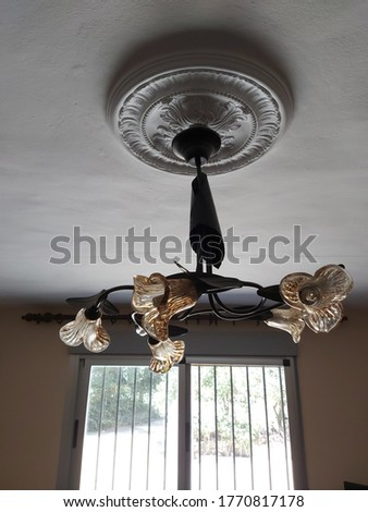 Beautiful yellow lanterns in shape of stars on ceiling. Ceiling lamp with starry shape on white ceiling. Decorative ceiling lamp. Yellow Lamp.