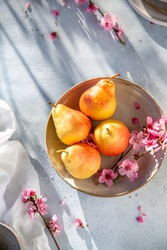 Beautiful yellow, pink pears in a plate on a blue background, sunny day, fresh fruits. overhead view copy space