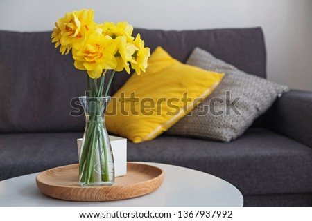 Beautiful yellow spring flowers in a vase standing in the living room on the coffe table. Modern cozy home.