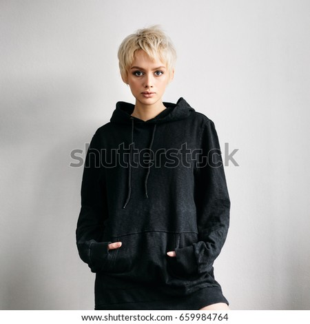 Beautiful young adult blonde woman in black hoodie on white wall #659984764