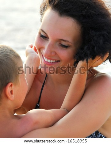 Beautiful young adult mather holding on knees  four years  son
